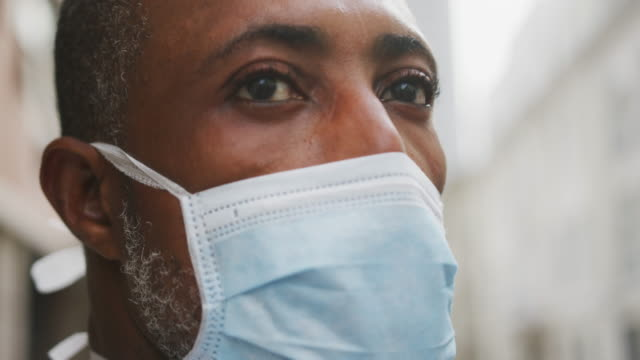 African american man on the go wearing coronavirus covid19 mask African American man out and about in the city streets during the day, wearing a face mask against air pollution and covid19 coronavirus. black people stock videos & royalty-free footage