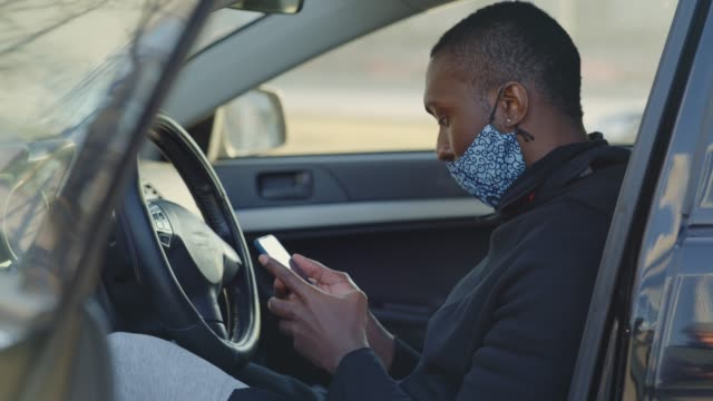 African American man out and about in the city streets during the day, wearing a face mask against air pollution and covid19 coronavirus, using his smartphone in a car. video