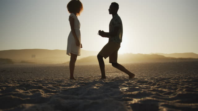 African American man proposing wedding at beach