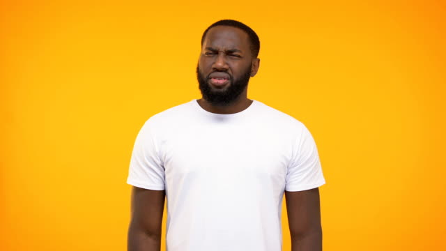 African american man showing confused reaction at camera on yellow background