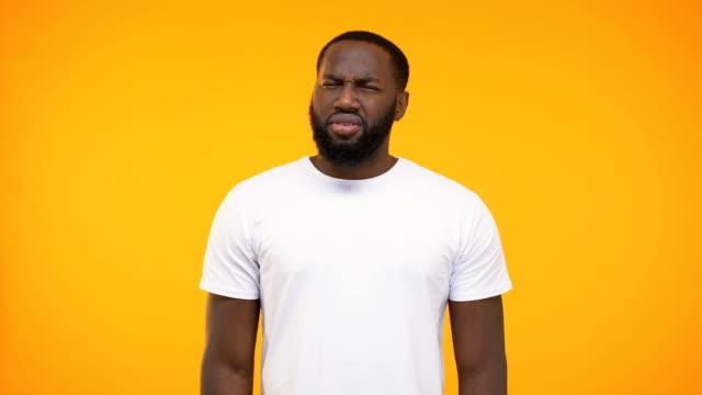 vidéos et rushes de homme d'afro-américain montrant la réaction confuse à l'appareil-photo sur le fond jaune - en désordre