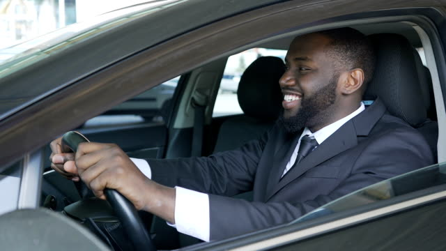 African American man sitting in expensive car satisfied and smiling, test drive video