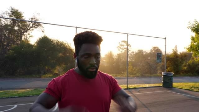stockvideo's en b-roll-footage met afrikaanse amerikaanse mens die zich en het verwarmen omhoog vóór zijn training uitrekt en opwarmt - twilight