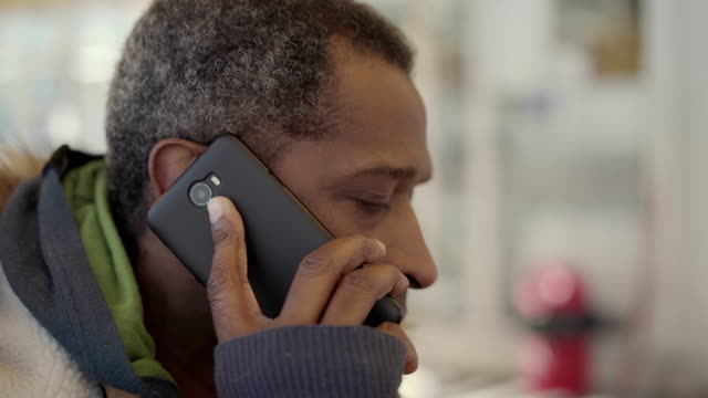 african american man talking by smartphone in cafe - orecchio video stock e b–roll