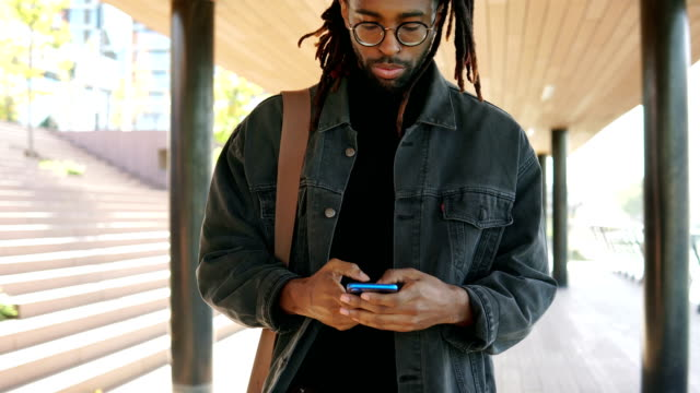 African american man texting on a phone African american man talking on a phone while walking outdoors locs hairstyle stock videos & royalty-free footage
