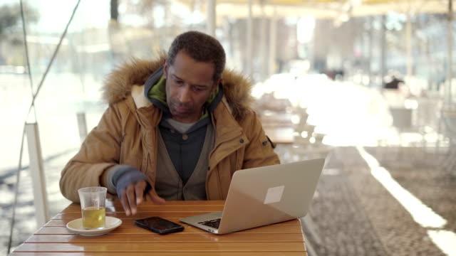 vídeos de stock e filmes b-roll de african american man using laptop and cell phone in cafe - esplanada portugal