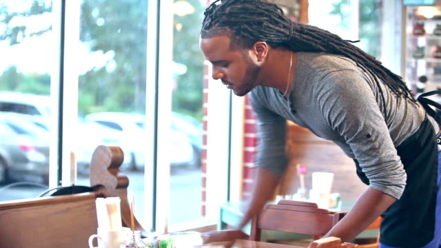 stockvideo's en b-roll-footage met african american man die werkt in de coffeeshop afvegen tafel - restaurant table