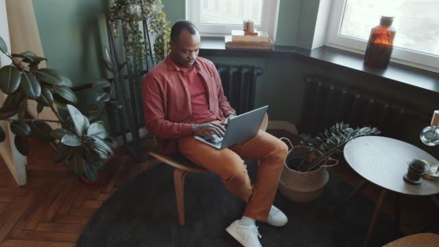 vídeos de stock, filmes e b-roll de homem afro-americano trabalhando em laptop na área de fuga de escritórios - confortável