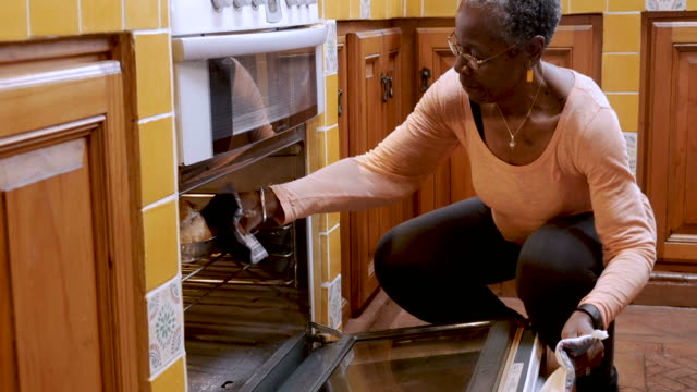 African American mature woman opens oven and removes fresh loaf of bread video
