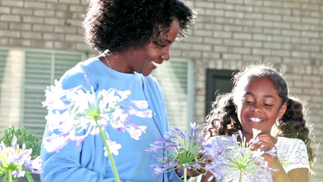 African American mother and daughter hugging in garden An African American mother and her 10 year old daughter standing in the yard outside their home, smelling pretty flowers in the garden before they hug. ornamental garden stock videos & royalty-free footage