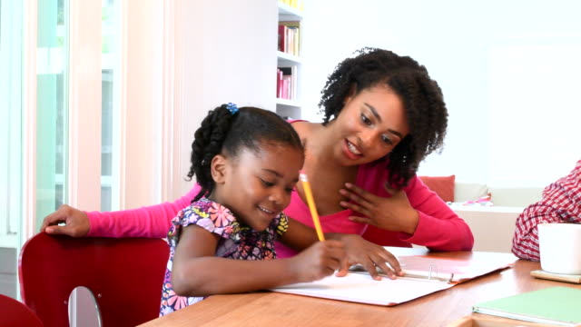 African American mother helping daughter do homework video