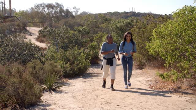 afrikansk amerikansk mor vandring med sin vuxna dotter - endast vuxna bildbanksvideor och videomaterial från bakom kulisserna