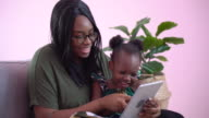 istock african american mother using tablet with her little daughter on couch at home . black girl lying on her mom learning online at home on sofa together . quarantine Home School 1271337158