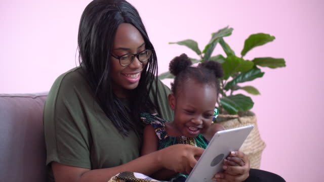 african american mother using tablet with her little daughter on couch at home . black girl lying on her mom learning online at home on sofa together . quarantine Home School