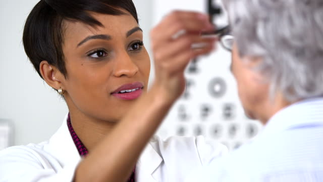 African American optometrist gives eyeglasses to senior woman video