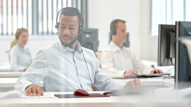 DS African American phone operator talking to a customer Medium dolly shot of an African American telephone operator at the call center for technical support, talking to a customer with his headphones on his head. call centre videos stock videos & royalty-free footage