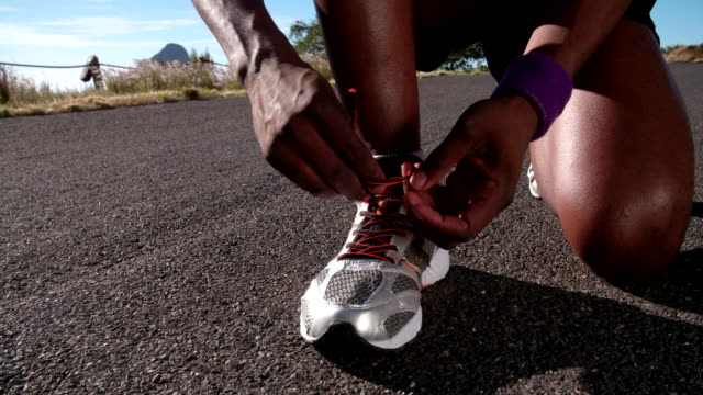 african american corridore annodare i suoi lacci rallentatore, primo piano - annodare video stock e b–roll