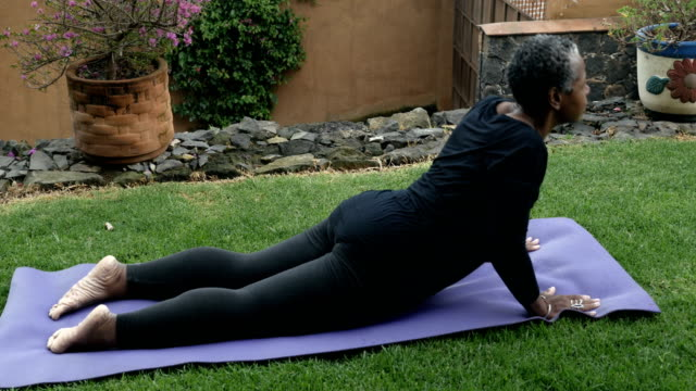 African American senior woman doing yoga cobra to downward dog pose