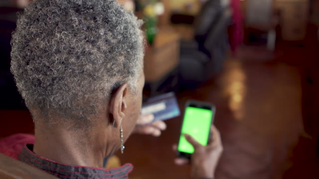 African American senior woman holding a credit card and a mobile phone