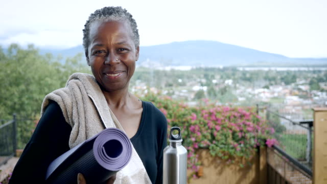 african american senior woman smiling and laughing portrait holding yoga mat - posizione corretta video stock e b–roll