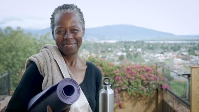african american senior kvinna ler och skrattar porträtt holding yogamatta - black woman towel workout bildbanksvideor och videomaterial från bakom kulisserna