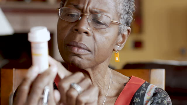 african american senior woman trying to read a pill bottle label in her hand - prescrizione medica video stock e b–roll