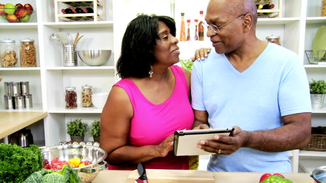 African American Seniors Kitchen Wireless Technology Senior African American couple standing kitchen counter holding wireless tablet reading recipe to use with fresh vegetables for healthy living lifestyle fat nutrient stock videos & royalty-free footage