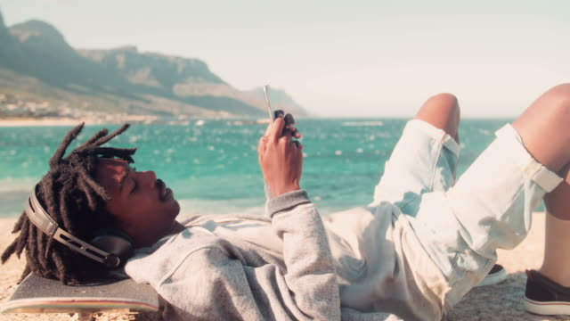African American Skater Resting and Looking at Smartphone at Sea video