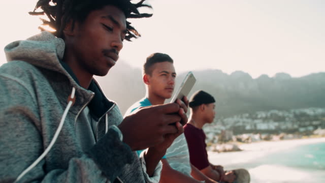 African American Skater Sitting and Looking at Smartphone Outsid video