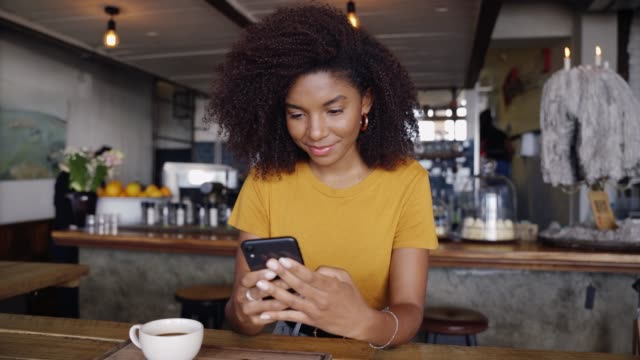 African American smiling female typing to boyfriend on smartphone sitting in trendy cafe next to hot cup of coffee Beautiful African American smiling female typing to boyfriend on smartphone sitting in trendy cafe next to hot cup of coffee. High quality 4k footage coffee shop stock videos & royalty-free footage