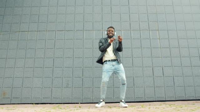 African American student having fun dancing in headphones in city street