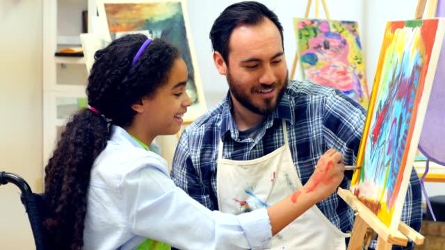 African American teen in wheelchair paints with art teacher