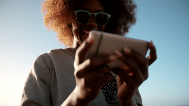 African American teenage hipster on her phone at the beach video