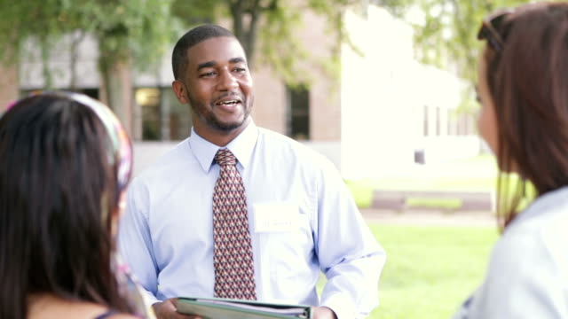 African American tour guide showing students around college campus Mid adult African American man is standing in courtyard of college. He is working as a tour guide and showing new students where to go. He's wearing business casual clothing and a nametag. Female prospective students are listening during campus tour. guidance stock videos & royalty-free footage