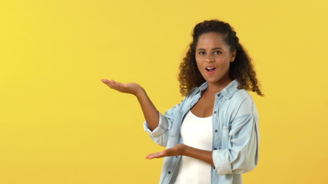 African American woman acting surprised while pointing hand to copy space