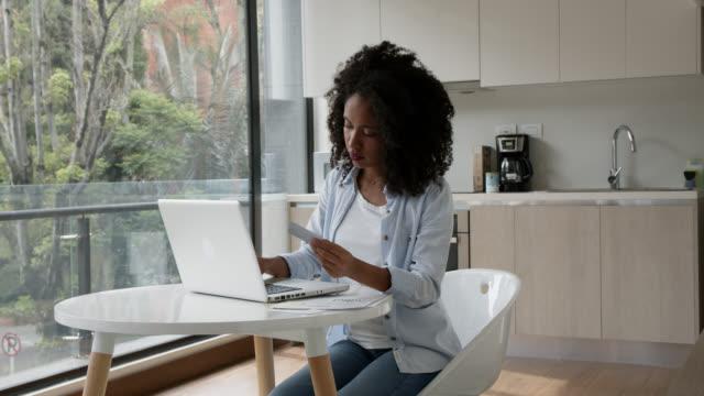 afrikanische amerikanische frau zu hause zahlen online-rechnungen mit laptop und kreditkarte - haushaltskosten stock-videos und b-roll-filmmaterial