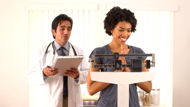 African American woman checking weight with doctor video