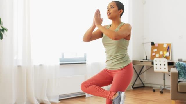 vídeos y material grabado en eventos de stock de afro american mujer haciendo postura de yoga en casa - cabello corto