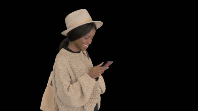 African American woman in a hat, texts on cell phone smiling, Alpha Channel