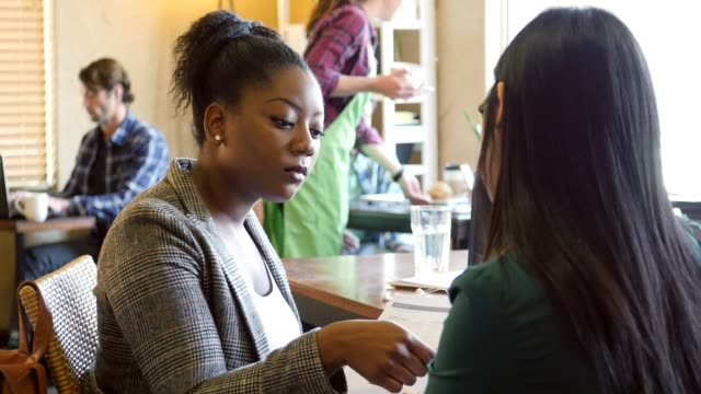 African American woman interviews young woman at a cafe video