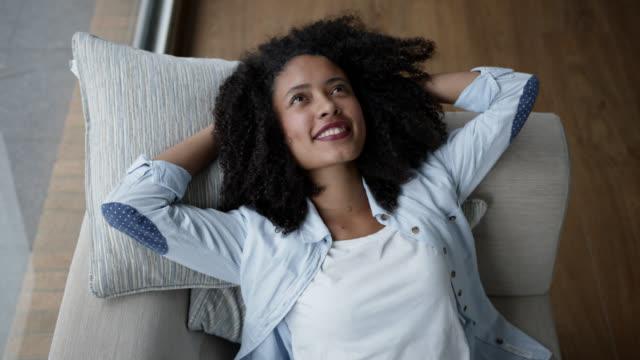 afrikanische amerikanerin liegt auf der couch und schaut tagträumend und lächelnd sehr glücklich - introspektion stock-videos und b-roll-filmmaterial