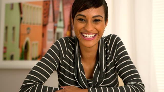 african american kobieta potakiwania głową i uśmiechnij się patrząc na kamery - virtual meeting filmów i materiałów b-roll