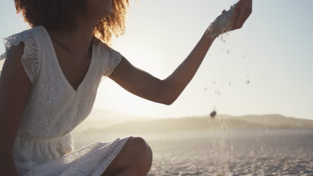 afroamerikanische frau spielt mit sand am strand - niedrig stock-videos und b-roll-filmmaterial