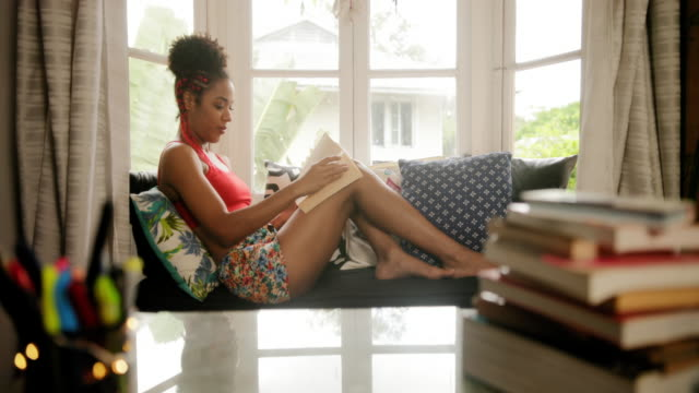 african american woman reading book at home near window - gelassene person stock-videos und b-roll-filmmaterial