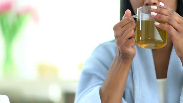 African American woman sick with flu drinking tea video