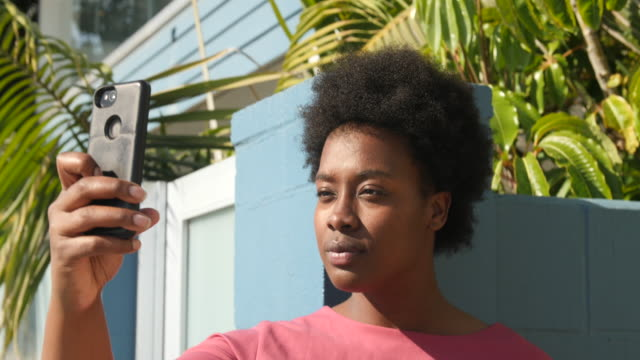 African american woman taking selfies Young african american woman taking selfie with her mobile phone. Curvy female with short hair standing outside and taking selfies with her smart phone. plus size model stock videos & royalty-free footage