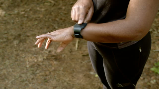 HD: Afrikanische amerikanische Frau, die ihre Herzfrequenz-Messgerät vor dem Lauf – Video