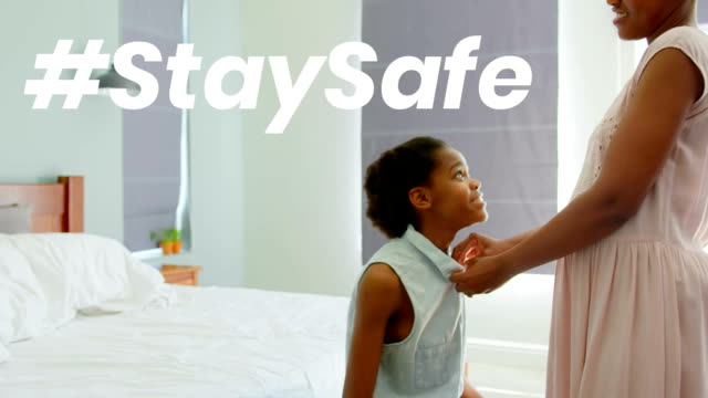 African American woman with her daughter at home with words Stay Safe during coronavirus pandemic