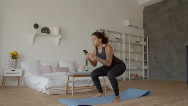 vídeos y material grabado en eventos de stock de mujer afroamericana con sentadillas telefónicas en casa - 20 a 29 años