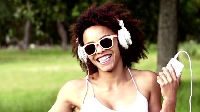 african american young woman listening to music on headphones video
